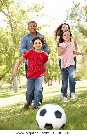 Family playing football in park