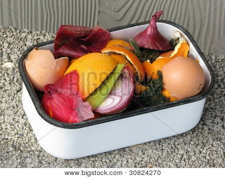 Colorful kitchen compost in a vintage white enamel container. Natural light.