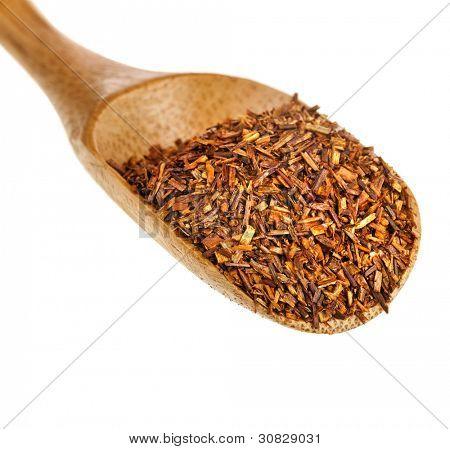 té rooibos suelto deja en la cuchara de madera, aislada sobre fondo blanco