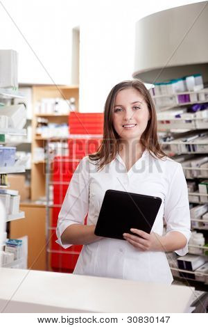 Portrait Of Smiling Female Pharmacist Holding Tablet Pc In Drugstore.