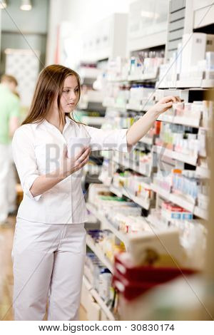 Attractive young pharmacist filling prescription