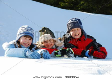 Three Kids Playing In The Snow