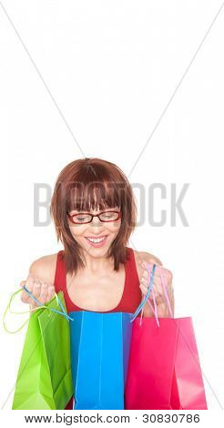 Happy redhead woman in glasses peering into the central blue shopping bag with an additional green and red bag in her hands