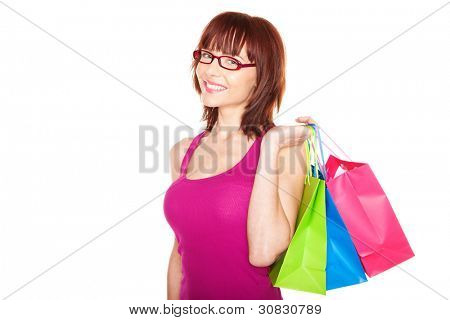 Smiling happy redhead woman in glasses with three colourful shopping bags over her shoulder