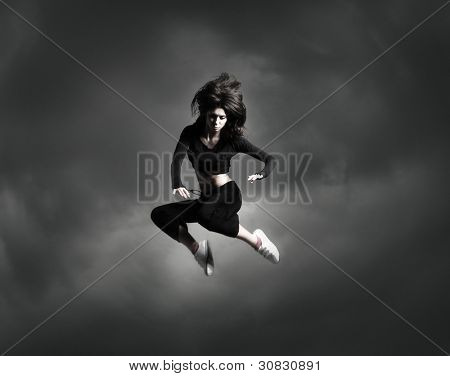 Young and sexy modern dancer over dramatic sky background