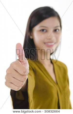 Young Asian female giving thumb up sign.