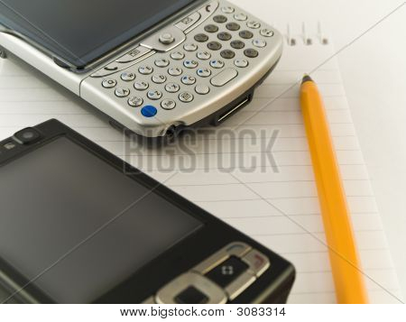 Mobile Phones And Pen On Notepad White Background