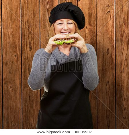 Middle aged cook woman holding a vegetable sandwich against a wooden wall