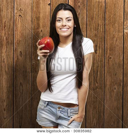 woman holding a delicious mango against a wooden background