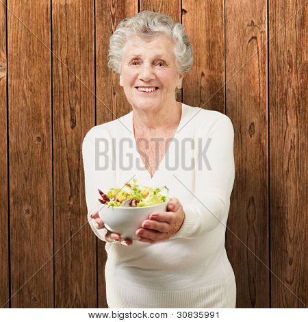 portrait of senior woman showing a fresh salad against a wooden wall