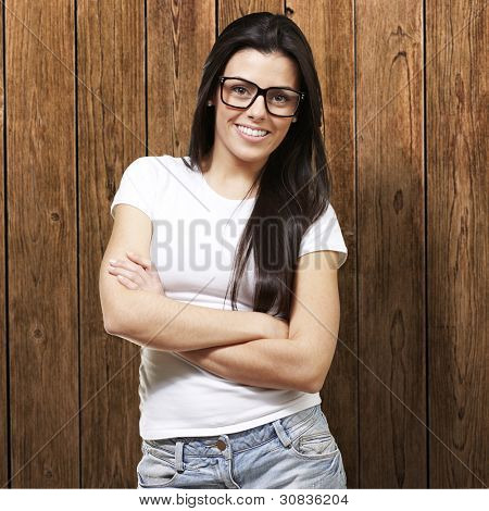 pretty young woman with glasses crossing her arms against a wooden background