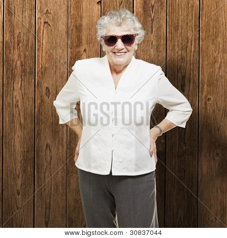 portrait of senior woman standing wearing sunglasses against a wooden wall