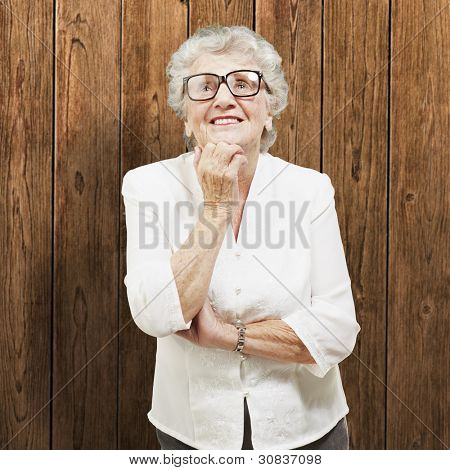 portrait of senior woman thinking and looking up against a wooden wall