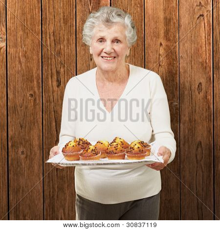 portrait of senior woman showing homemade muffins against a wooden wall