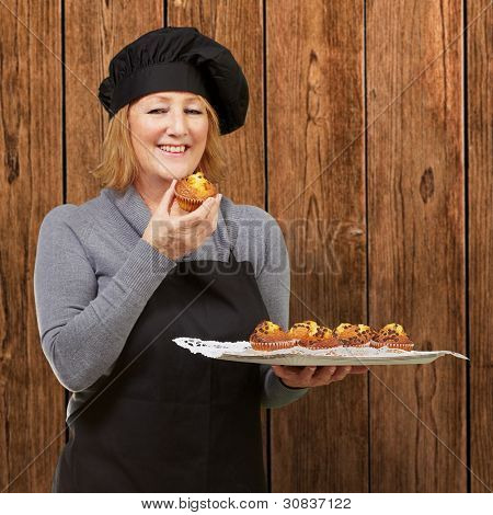 portrait of middle aged cook woman holding a homemade muffin against a wooden wall