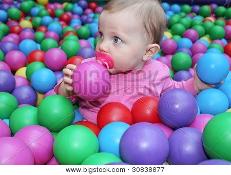 Adorable baby girl surrounded by balls