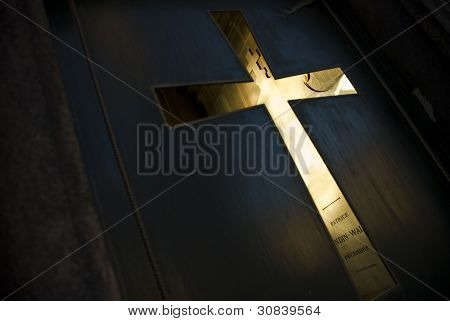 Cross in door at tomb cemetery