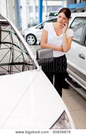 Woman thinking about buying a car but looking lost