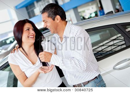 Couple at the dealer buying a car and looking happy