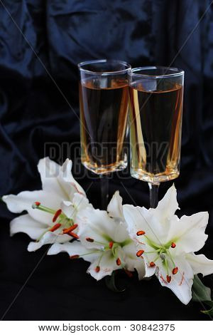 Glasses With Wine And Lily Flower On Black Silk