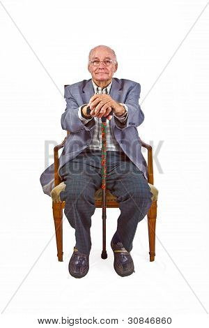 Old Man Sitting In The Armchair With His Walking Stick