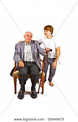 Old Man Sitting In The Armchair With His Grandchild Standing Beside Him