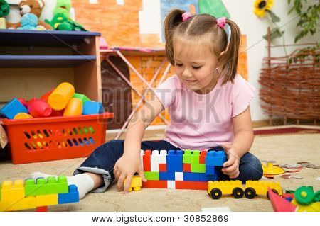 Little girl is playing with building bricks in preschool while sitting on floor