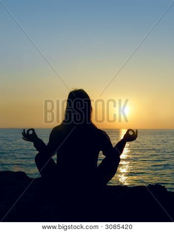Woman Silhouette Making Yoga Over Sunset Sea Background