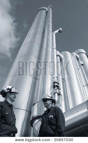 zwei Ölarbeiter mit riesigen Gas- und Ölleitungen im Hintergrund, duplex blau toning Konzept