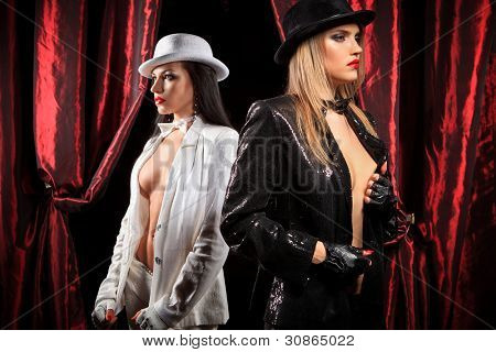 Cabaret performers wearied white and black clothes on stage looking at the audience