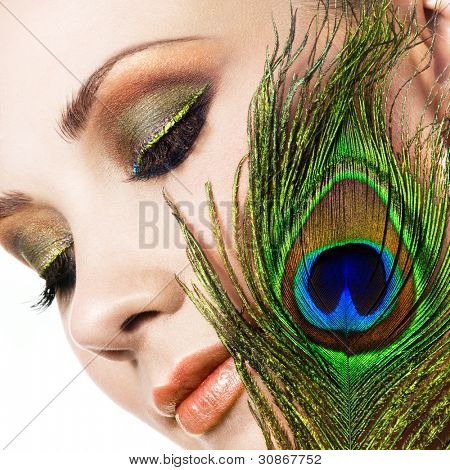 Woman with colorful makeup and peacock feather