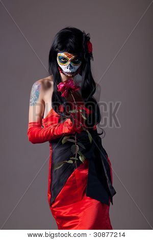 Sugar skull girl with rose, studio shot