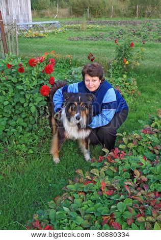 woman with dog amongst flowerses