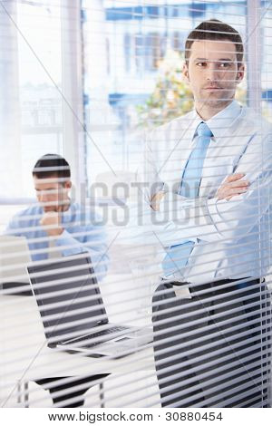 Young businessman standing in bright office, looking through blind, thinking.?