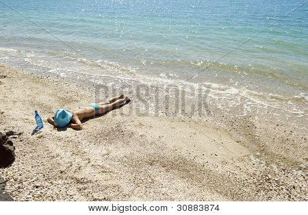 A woman sunbathing on beach