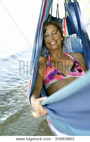 happy woman sitting in hammock
