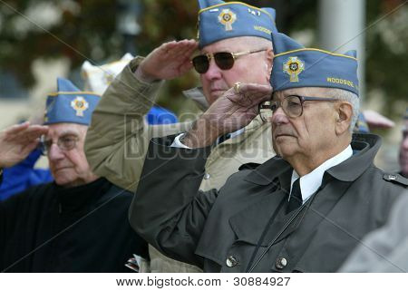 NEW YORK - NOV 11: Members of the American Martyrs Catholic War Veterans, Post 1772 of Bayside salute at a Veteran's Day Memorial service at St. John's University November 11, 2005 in Queens, NY.