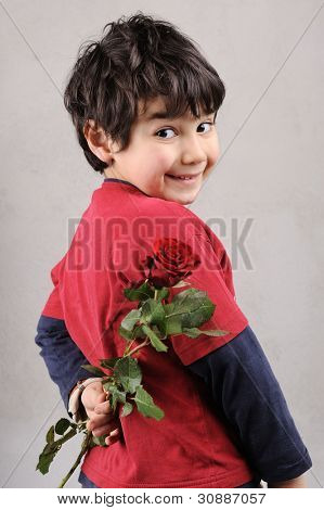 Handsome little boy with a red rose behind his back