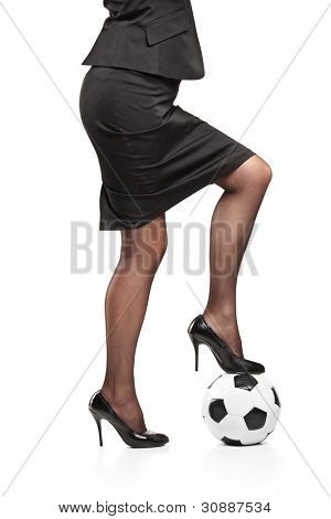 Woman in high heeled shoes standing on a soccer ball isolated on white background