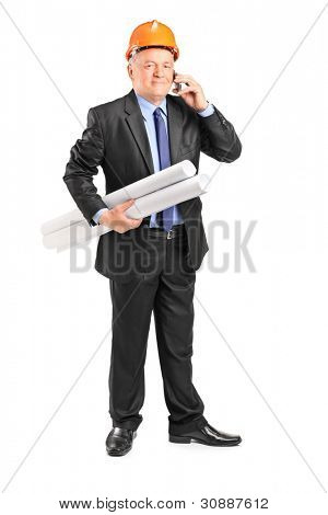 Full length portrait of a mature construction worker holding blueprints and talking on a phone isolated on white background