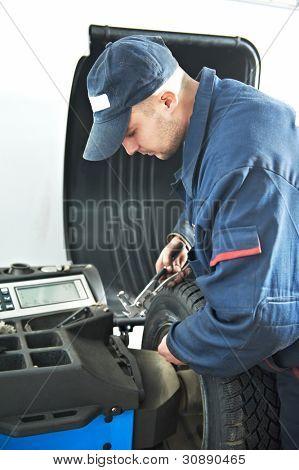 在汽车轮胎配件和平衡调整使用特殊设备的机械修理工
