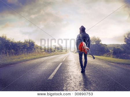 Young musician walking on a countryside road with a guitar on his shoulder