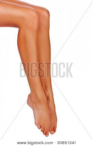 Closeup of a young woman tanned legs on white studio background