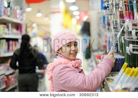 Beautiful smiling little girl in bookstore