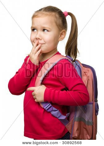Portrait of a cute little schoolgirl with backpack thinking about something, isolated over white