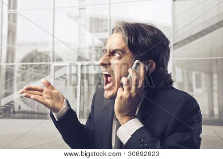 Angry businessman screaming on the mobile phone