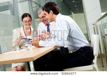 Three business partners sitting in office and sharing their ideas