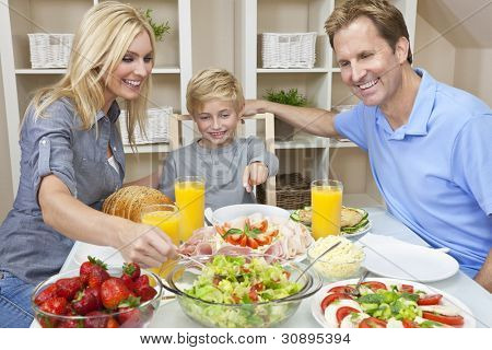 An attractive happy, smiling family of mother, father and son eating salad and healthy food at a dining table