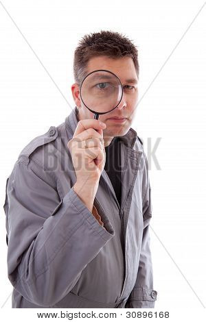 Man With Raincoat Is Looking Through Magnifying Glass