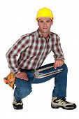 stock photo of bender  - Tradesman holding a tube bender - JPG